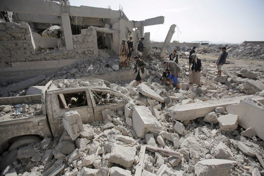 People inspect the rubble at a Houthi detention center destroyed by Saudi-led airstrikes.