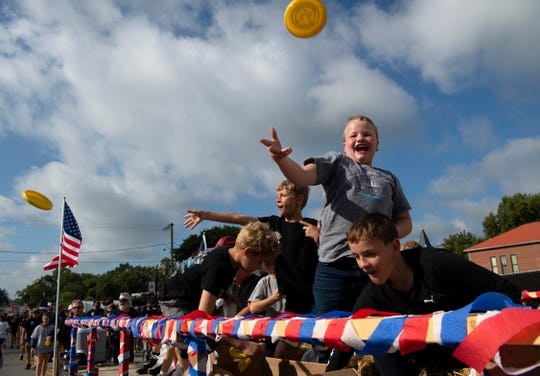 Youngsters aboard the International Brotherhood of Electrical Workers (IBEW) Local 1393 float toss out tiny flying discs at the annual Labor Day Parade in Princeton, Ind., Monday morning.