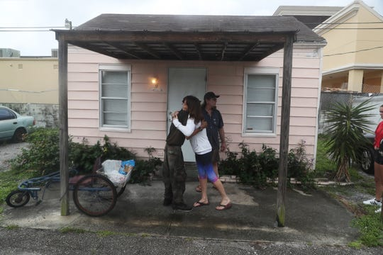 """Stacey McKindles, a resident of Martin County Florida gives Bob """"Cowboy"""" Marschat a hug in thanks Monday, September 2,  2019 for watching a home of a family friend at Ocean Tide trailer park. Marschat says he wasn't leaving no matter what the path of Hurricane Dorian. He lives with a friend, Alfred """"Ace"""" Gritner in a mobile home. Marschat and Gritner live a mandatory evacuation zone but are staying."""