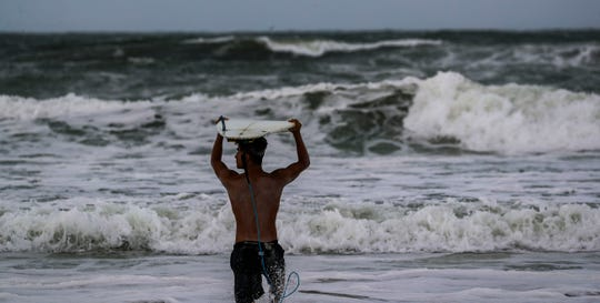 "Josue Amador of Daytona looks to surf in the rough water. ""This is the best time to surf and you have to take advantage of it"", he said. The Daytona Beach area has been put on mandatory evacuation, yet people wanted to see and use the beach one last day."