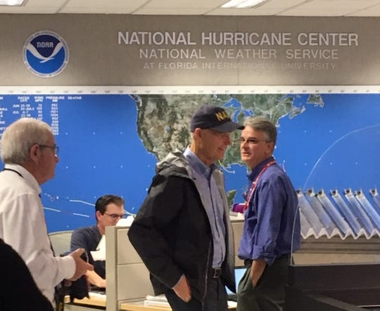 Meteorologist Joel Cline in the background during U.S. Senator and former Florida Gov. Rick Scott's visit to the National Hurricane Center in Miami on Sept. 2, 2019. Cline assists at the National Hurricane Center during major storms.