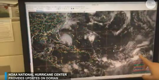 A forecaster with the National Hurricane Center points to a tropical wave in the Atlantic.