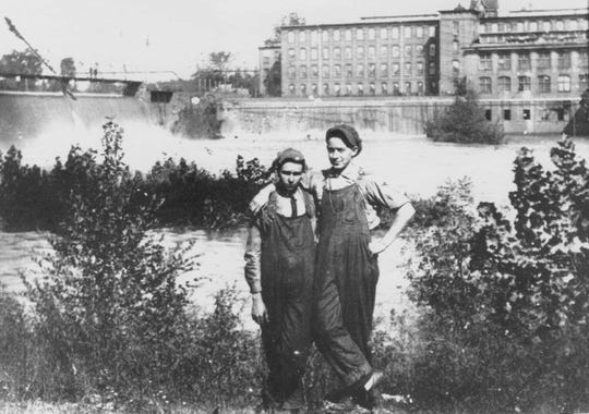 Mill workers in the 1920s pose for the camera on the Anderson side of the Saluda. Behind them are Piedmont #1, the dam and the footbridge over the river.