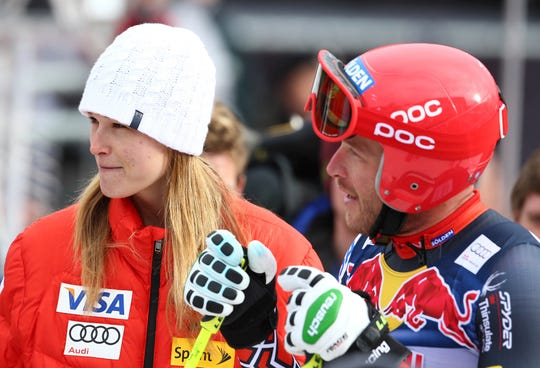 In this Jan. 23, 2014, file photo, Bode Miller talks to his wife, Morgan, in the finish area of men's skiing World Cup downhill training in Kitzbuehel, Austria. Miller is moving his family to Montana part time after a tumultuous year that included the tragic drowning of his toddler daughter. Miller says 19-month-old Emeline Miller's death made him sharpen his focus on his four other children, and with twins due this fall, he decided the time was right to head to the mountains. The family will split their time between homes in Southern California and Big Sky, Mont. (AP Photo/Giovanni Auletta, File)