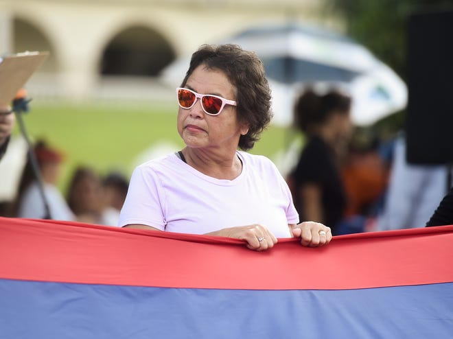 Gov. Lou Leon Guerrero helps hold the Guam flag during the Fanohge: CHamoru March for Self-Determination's opening ceremony in Adelup on Sept. 2, 2019.