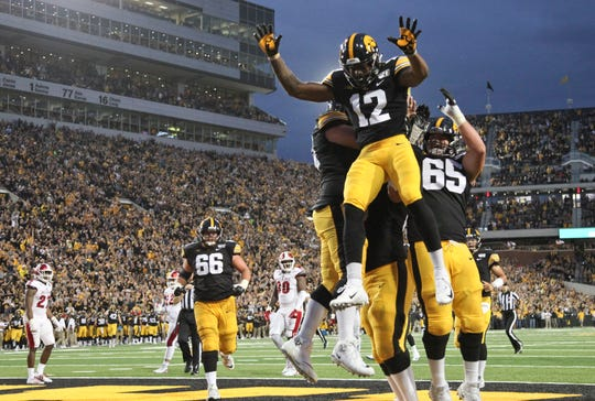 Iowa's Brandon Smith (12) is joined by center Tyler Linderbaum (65) and a host of teammates after his 9-yard touchdown catch in the second quarter of the Hawkeyes' 38-14 win against Miami.