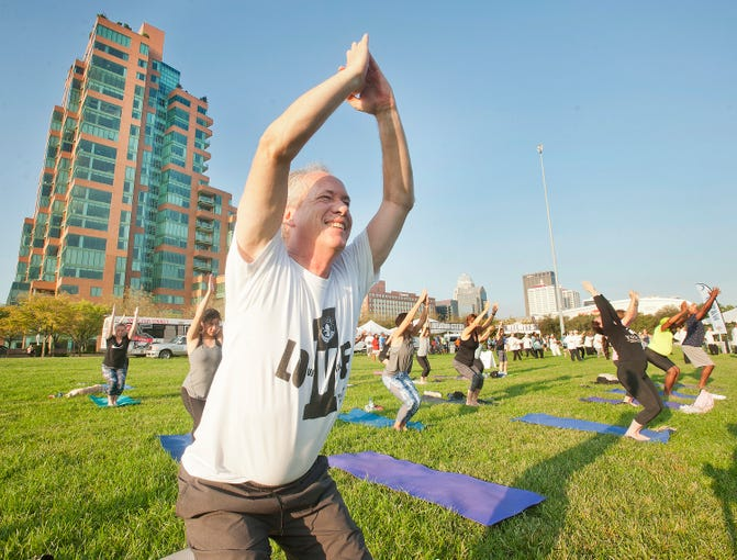 """Louisville, Ky. Mayor Greg Fischer practices some warm-up yoga at the city's 15th annual Labor Day """"Hike, Bike & Paddle"""" event on Sept. 2, 2019."""