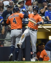 Astros centerfielder George Springer celebrates with third baseman Alex Bregman after hitting a solo home run in the 10th inning Monday at Miller Park.