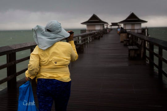 Pia Woollard holds onto her hat as she walks down the Naples Pier on Monday, September 2, 2019. A strong line of thunder storms moved through Naples on Monday afternoon, with wind gusts of up to 45mph, according to the National Weather Service in Miami.