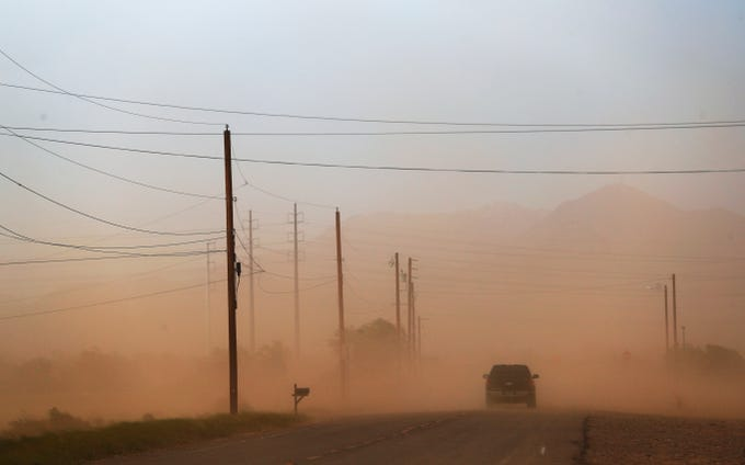 A car drives into blowing dust on N. Horne Ave. on the Salt River Pima Maricopa Indian Reservation during a monsoon dust storm Sept. 1, 2019.