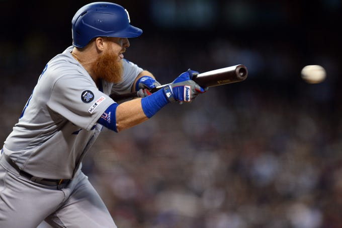 Sep 1, 2019; Phoenix, AZ, USA; Los Angeles Dodgers third baseman Justin Turner (10) bunts against the Arizona Diamondbacks during the ninth inning at Chase Field. Mandatory Credit: Joe Camporeale-USA TODAY Sports