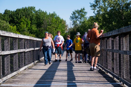 People walk across the trestle bridge spanning Mill Creek along the Wadhams-to-Avoca Trail Monday, Sept. 2, 2019, during the annual Trek the Trestle Labor Day Walk.