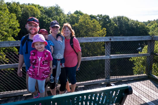 Josh and Holly Semrow, left and second from right, pose for a photo with their kids Daisy, 4, Henry, 3, and Carson, 5 months, and their friend Sharon Raditz, right, on the trestle bridge along the Wadhams-to-Avoca Trail Monday, Sept. 2, 2019, during the annual Trek the Trestle Labor Day Walk.