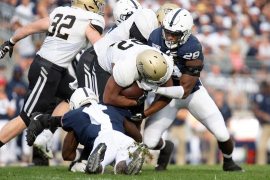 Penn State defenders Jayson Oweh (28) and Cam Brown (6) tackle Idaho running back Aundre Carter (22) in the third quarter of an NCAA college football game against Idaho in State College, Pa., on Saturday, Aug. 31, 2019. (AP Photo/Barry Reeger)
