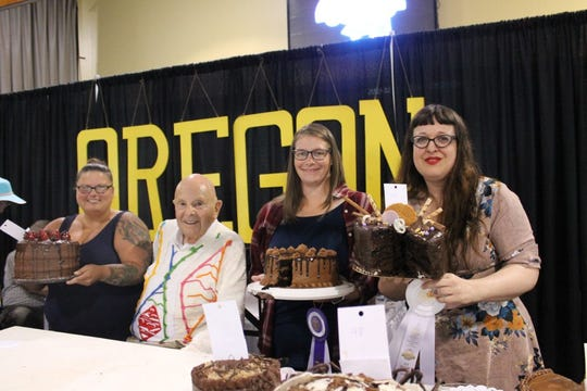Gerry Frank with the top 3 finishers of the 60th Annual Gerry Frank Chocolate Cake Contest on September 1, 2019, at the Oregon State Fair. From left to right: 2nd place finisher Jamie Hendrickson of Monmouth, Gerry Frank, 1st place finisher Jenn Hearn of Keizer, and 3rd place finisher Suzanne Akin of Bend.