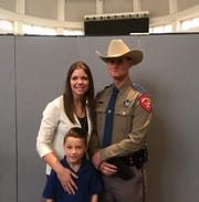 DPS state trooper Chuck Pryor stands in uniform with his wife and son. Pryor was shot in the face during the Odessa-Midland shooting on Saturday, Aug. 31, 2019.
