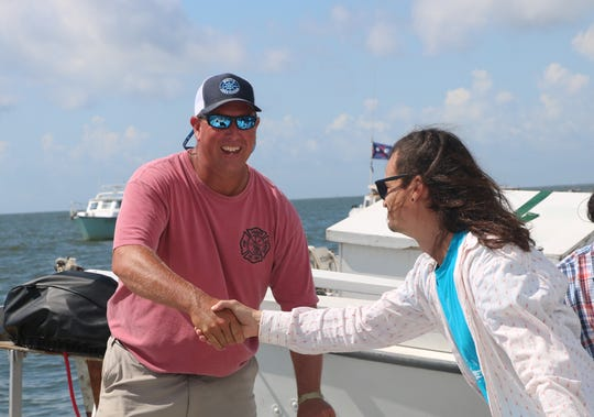 David Gladden congratulates Capt. Shawn Ridgley of the skipjack Ida May after Ridgley captured his third win in a row at the 60th annual Skipjack Races at Deal Island Sept. 2, 2019.