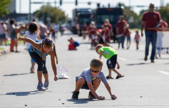 Kevin Ives, 4, scrambles to collect candy during the Labor Day Parade on Monday, Sep. 2, 2019, in Springfield, Mo.