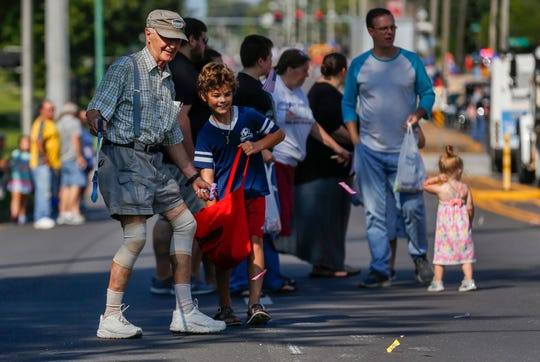 Bill Bultas helps his grandson Flynn Bultas, 9, collect candy during the Labor Day Parade on Monday, Sep. 2, 2019, in Springfield, Mo.
