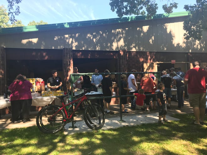 People line up for food at a Labor Day picnic in Riverside Park Monday afternoon, Sept. 2.