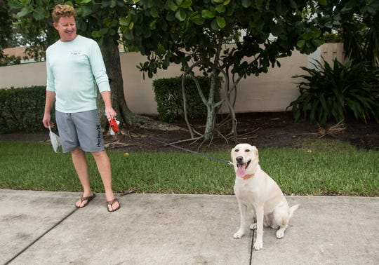 Jason Chism and his dog, Treadwell, stop on Jensen Beach Causeway on Monday, Sept. 2, 2019, while out for a walk before Hurricane Dorian's effects.