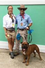 """Katy Dombrowski, left, and Grant Homa with Kato, dressed as Jurassic Park guides, won the costume contest at the 2019  """"Chewrassic Bark"""" pup crawl in downtown Stuart."""