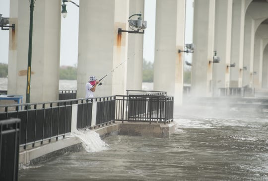 A man fishes from under the Jensen Beach Causeway as the Indian River Lagoon splashes around over the walkway on Monday, Sept. 2, 2019, as Hurricane Dorian approaches the region.