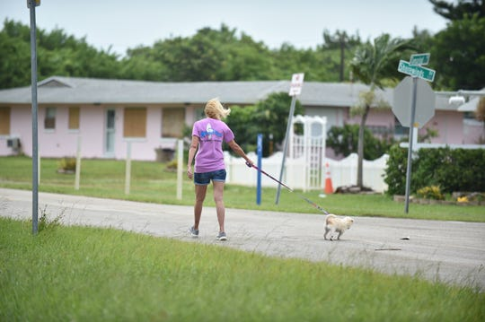 Cindy Rohn, co-owner of Sharky's restaurant on North Hutchinson Island, walks her puppy, Yum Yum, near her business ahead of Hurricane Dorian's arrival Monday, Sept. 2, 2019, in St. Lucie County.