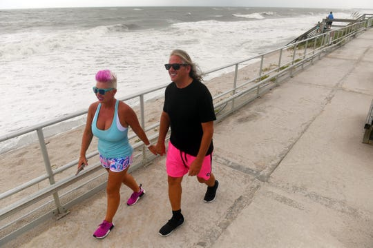 """Patrick Sanders and Erika Hugunin walk along the Humiston Beach boardwalk on Monday, Sept. 2, 2019, as they watch the high surf come ashore ahead of Hurricane Dorian. """"We're going to stay and ride the storm out,"""" said Sanders. Hurricane Dorian, a category 5 storm, is slowly making its way toward the Florida Coast and is expected to bring damaging winds and flooding."""