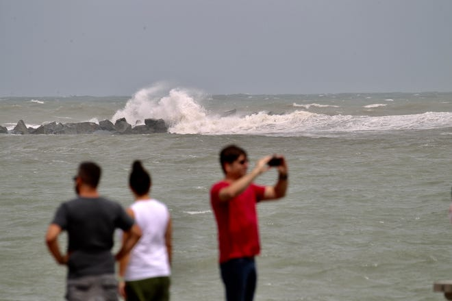 Waves crash into the north jetty as onlookers watch the rough surf from the south jetty at Fort Pierce Beach on Monday, Sept. 2, 2019, as heavy swells from Hurricane Dorian stir the water along Treasure Coast beaches.