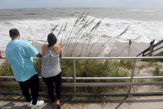 Local residents gathered Monday, Sept. 2, 2019, at the boardwalk at Humiston Beach to watch the large waves and surf come ashore ahead of Hurricane Dorian. The storm has stalled over The Bahamas and is expected to bring damaging winds, flooding and cause coastal erosion.