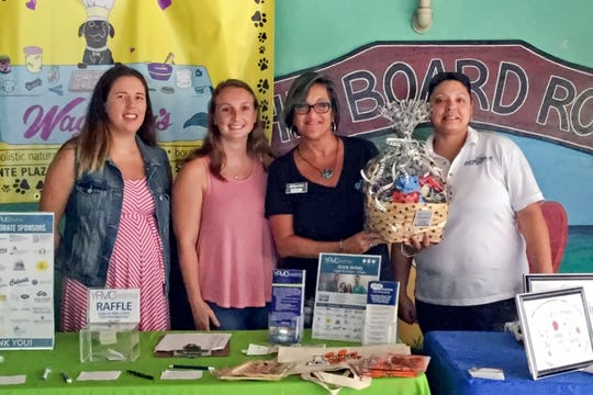"""Event Sponsors Jessica Grassi and Caitlin Hartley, left, with Young Professionals of Martin County, Karen Hopping with Wagnolia's Pet Boutique & Bakery and Lesli Graham with Doggiedate.net at the 2019 """"Chewrassic Bark"""" pup crawl in downtown Stuart in support of the Humane Society of the Treasure Coast."""