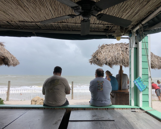 "Brothers-in-law Paul Maneos, 55 (left) and Steve Thorp, 63 (right) sit together under a shuttered pavilion of Mulligans Beach House at 3384 Ocean Drive in Vero Beach the afternoon of Sept. 2 as Hurricane Dorian slowly creeps north. ""This beats being inside any day,"" Maneos said. ""We just hope everyone stays safe."""