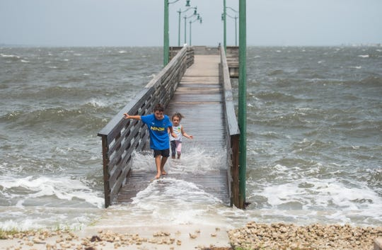 Antonio Cisneros, 8, runs off the pier followed by his sister, Esmee Cisneros, 3, at Jensen Beach Causeway Park in Martin County on Monday, Sept. 2, 2019, as Hurricane Dorian approaches the region. Their father, Sergio Cisneros, said he brought the children to learn about the effects of a powerful storm.