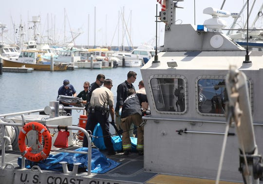 Santa Barbara city search-and-rescue team members along with Santa Barbara County sheriff's officers move a recovered body on the dock at Santa Barbara Harbor on Monday. The body was recovered from a dive boat fire near Santa Cruz Island early Monday.