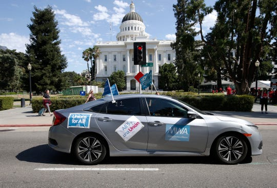 In this Aug. 28, 2019, photo, supporters of a measure to limit when companies can label workers as independent contractors drive their cars past the Capitol during a rally in Sacramento, Calif. California lawmakers are debating a bill that would make companies like Uber and Lyft label their workers as employees, entitling them to minimum wage and benefits.