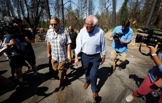 In this Aug. 22, 2019, file photo, Democratic presidential candidate Sen. Bernie Sanders, I-Vt., right, talks with area resident Michael Ranney, left, as he tours a mobile home park that was destroyed by last year's wildfire in Paradise, Calif.