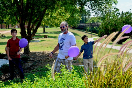 Vern Landavazo, center, took part in a balloon release to honor his daughter, Lauren, who was shot and killed three years ago while walking home from McNiel Junior High School. The balloon release took place Monday at the Angel of Hope Memorial Garden behind Kay Yeager Coliseum in downtown Wichita Falls.