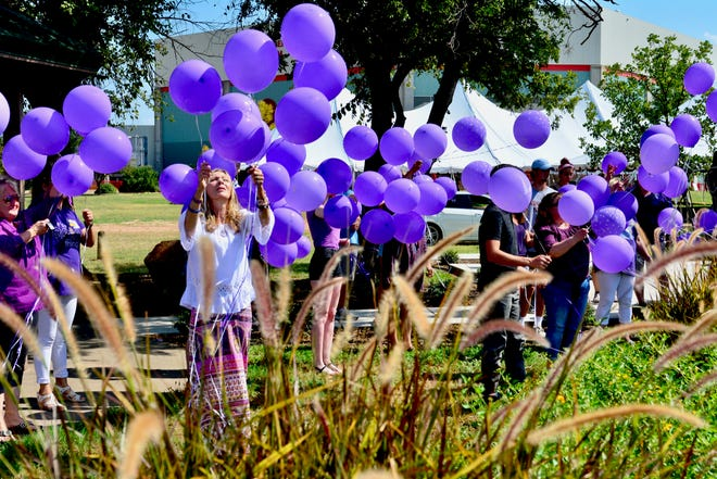 Bianka Landavazo, center in the white shirt, releases balloons Monday at the moment three years ago when her daughter, Lauren, 13, was shot and killed while walking home from school. Released at the Angel of Hope Memorial Garden beyond Kay Yeager Coliseum, the purple balloons represent Lauren's favorite color.