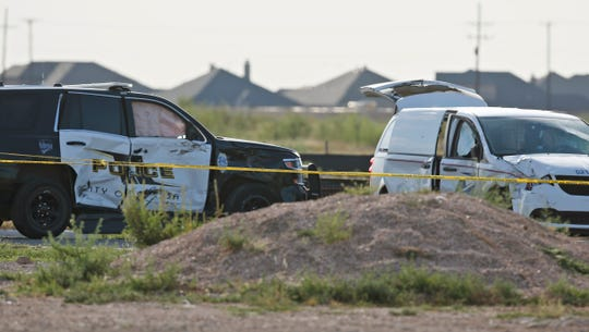 A city of Odessa police car, left, and a U.S. mail vehicle, right, which were involved in Saturday's shooting, are pictured outside the Cinergy entertainment center, Sunday, Sept. 1, 2019, in Odessa, Texas.