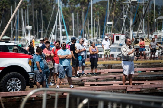 Bystanders watch and record video as United States Coast Guard members transfer a body at the Santa Barbara Harbor on Sept. 2, 2019.
