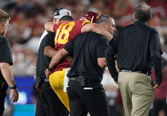 Southern California quarterback JT Daniels is helped off the field after suffering a knee injury against Fresno State.