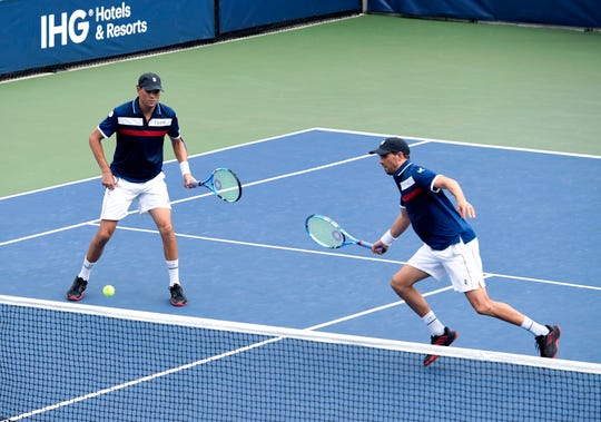 Mike Bryan, right, returns a shot as his brother Bob Bryan, looks on during their first-round doubles match at the U.S. Open.