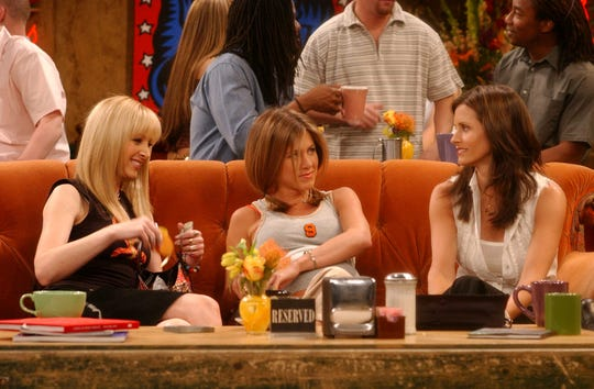 """Phoebe (Lisa Kudrow), Rachel (Jennifer Aniston) and Monica (Courteney Cox) relax on the orange Central Perk couch in a scene from NBC's """"Friends."""""""