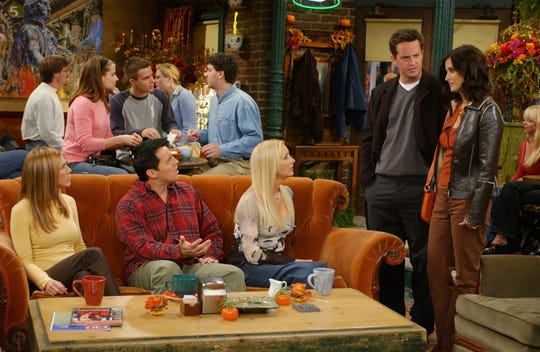 """Jennifer Aniston, Matt LeBlanc, Lisa Kudrow on the couch, and Matthew Perry and Courteney Cox (standing) in an episode of NBC's """"Friends,"""" celebrating its 25th anniversary in 2019 with a sofa tour."""