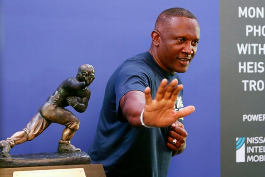 Former Notre Dame receiver Tim Brown poses with the Heisman Trophy before the school's game against Michigan in 2018.