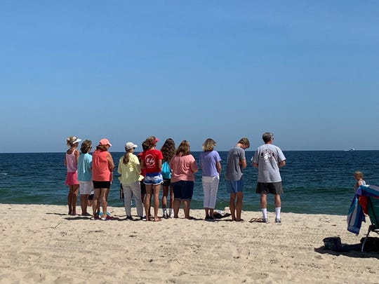 Local residents gathered on the beach in Spring Lake Tuesday to pray for the family of 15-year-old Josiah Jeremiah Robison, who vanished in the surf over the weekend.