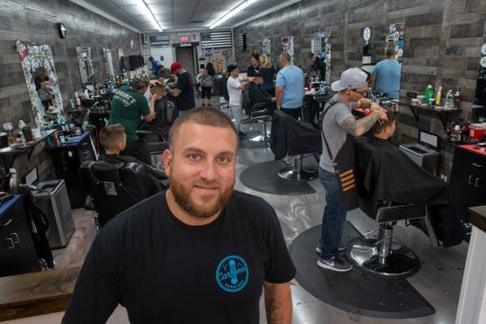 Chris Carbone, owner of Carbone's Barber Shop in Brick, with his barbers working behind him on 09/03/19.