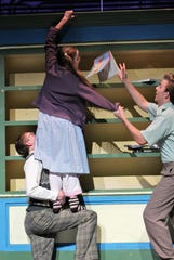 """Fairy Mae (Kyla Sutton) lets a book slip from a tall shelf as Hannibal (Joshua Larum) holds her up and Jeffrey (Caleb Speights) tries to catch the falling object in this early rehearsal scene from Wylie High's """"The Curious Savage,"""" which opens Sept. 19."""