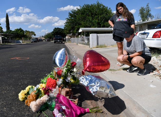 Ashley Salazar (kneeling) and Alyssa Baeza, both of Midland, pray over the memorial to slain postal worker Mary Granados in Odessa Monday Sept. 2, 2019. The letter carrier was one of seven killed Saturday by Seth Ator, 36, who went on a shooting spree Saturday and struck nearly two dozen people with gunfire.
